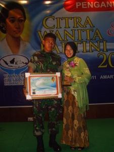 Ny. Aidah didampingi anaknya, Sandi Al Mizan, saat menerima penghargaan