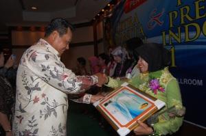 Ny. Aidah mendapatkan ucapan selamat dari Mardiyanto saat menyerahkan penghargaan