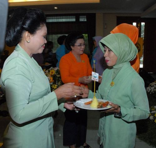 Ny. Aidah (kanan) menerima pucuk tumpeng dari Ny. Rini Murdjito (kiri)